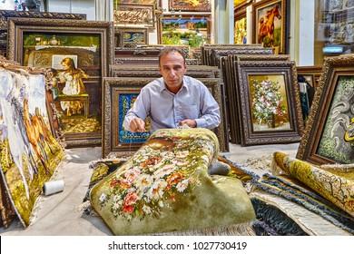 Tehran, Iran - April 29, 2017: A showroom of oriental rugs  on the Grand Bazaar of Tehran, a man weaves a Persian carpet.