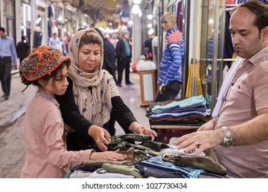 Tehran, Iran - April 29, 2017: Iranian family on Tehran Grand Bazaar, mother and daughter choose clothes in the textile department.