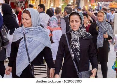 Tehran, Iran - April 29, 2017: Women in hijabs walking in a street crowd near Tehran Grand Bazaar.