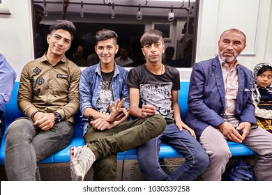 Tehran, Iran - April 29, 2017: cheerful Iranian men sit in the subway train car and smile.