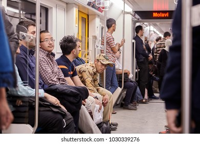 Tehran, Iran - April 29, 2017: Iranian men stand and sit in the new modern underground train.