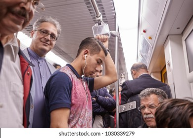 Tehran, Iran - April 29, 2017: Iranian men of different ages ride the subway, one of them listens to music on headphones, another stands and smiles.