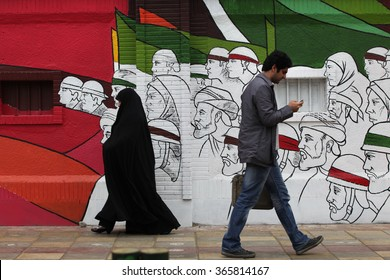TEHRAN, IRAN - APRIL 3, 2012: People walking in Imam Khomeini Street with street art wall in background, in central Tehran, Iran.