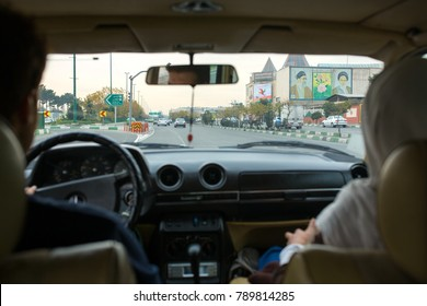 Tehran, Iran - December 1, 2015: Iranian couple driving their car in Tehran streets passing by portraits of the supreme leaders of Iran, Sayyed Ali Hosseini Khamenei & Ruhollah Khomeini