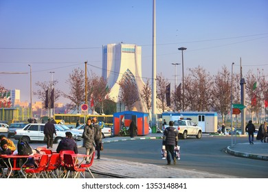 TEHRAN, IRAN - JAN 09: Beautiful city view - unidentified local people go along the street at the background of Azadi Tower on January 9, 2019 in Tehran, the capital of Iran, Middle East