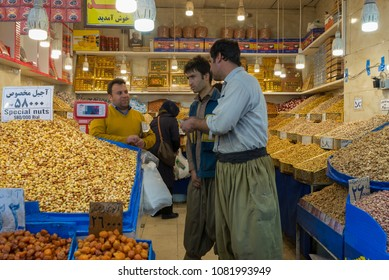 Tehran / Iran - March 02 2018: In spite of increasing political conflict, Kurdish men are friendly with Persian shopkeeper