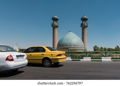 TEHRAN, IRAN - MAY 2017: Two Iranian made cars passing a mosque in Tehran (plate altered).