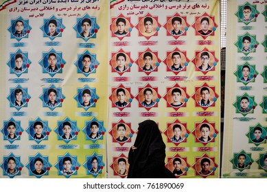 TEHRAN, IRAN - MAY 2017: A veiled woman passes a poster in front of a school in the center of Tehran.