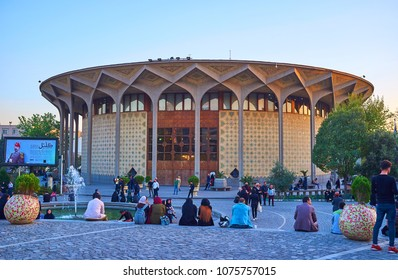 TEHRAN, IRAN - OCTOBER 24, 2017: Locals enjoy their evening time in Daheshgu Park with a view on beautiful edifice of Teatre Shahr built in persian style, on October 24 in Tehran.