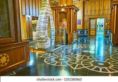 TEHRAN, IRAN - OCTOBER 25, 2017: The entrance hall of Malek museum is decorated with patterns on the floor, carved wooden walls and buta (painsley) installation of books, on October 25 in Tehran