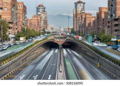 TEHRAN, IRAN - OCTOBER 26, 2016: Flow of traffic in, out and around Tohid Tunnel with Milad Tower and Alborz Mountains in Background. This is the third longest urban tunnel in Middle East.