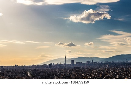 Tehran skyline in a beautiful cloudy day with golden hour light Tehran-Iran cityscape with Milad tower in photo and white clouds and lovely blue sky