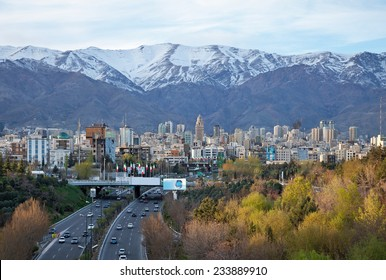 Tehran skyline and greenery in front of snow covered Alborz Mountains as viewed from atop of Nature Bridge.