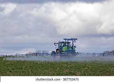 Teignmouth, Devon UK, March 3 2016 - Showing a farmer in a tractor spraying crops with insecticide, showing the sprayer in operation whilst attached to the back of a blue tractor