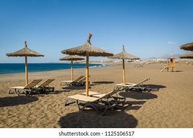 Tejita sand beach with long chairs and umbrellas. Tenerife, Spain.