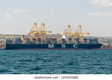 Tekirdag / Turkey - August 8th 2018: Container ship which is full of containers docked at port. Cranes are loading containers to cargo ship.