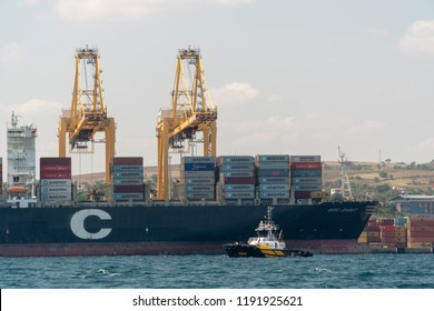 Tekirdag / Turkey - August 8th 2018: Container ship which is full of containers docked at port. Cranes are loading containers to cargo ship. Meanwhile Pilot boat checking it.
