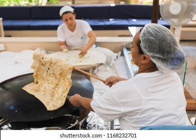 TEKIROVA, TURKEY - AUGUST 04, 2018: Two Turkish women are sitting and cooking Turkish Gozleme. Turkish Gozleme baked on sheet iron.