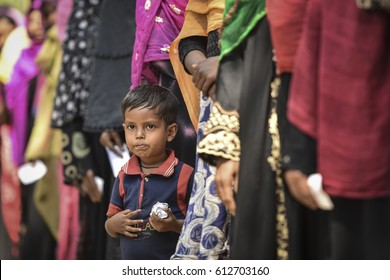 TEKNAF, BANGLADESH - APRIL 1, 2017 : One child Rohingya refugees await aid in Kutupalong Rohingya camps near Cox's Bazar, Bangladesh