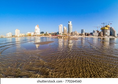Tel Aviv beach coast with a view of Mediterranean sea and skyscrapers, Israel.