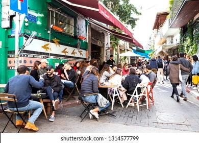 Tel Aviv, Carmel Market, Israel - December 28, 2018:A young people socialising and enjoying the food at outside restaurant in famous Carmel market, Tel Aviv - Yafo, Israel