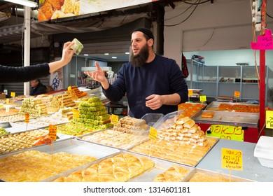 Tel Aviv, Carmel Market, Israel - December 28, 2018:A young man with beard selling traditional, oriental sweet dessert - baklava - at Carmel Market stall in Tel Aviv - Yaffo, Israel