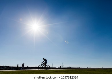 Tel Aviv, Israel - 17 September 2012: Silhouette of a cycler passing on a park path on a clear summer day, afternoon sun shining.