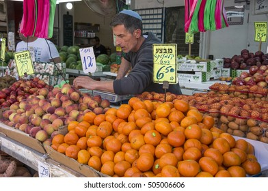 TEL AVIV, ISRAEL - APRIL 30, 2015: Seller, placing the fruit in her stall, in the Carmel Market