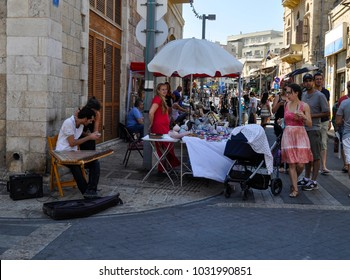 Tel Aviv, Israel, August 2017, bazaar or suk market with diverse shops and restaurant and multi national people walking around. A young man is playing a traditional instrument ''qanun''