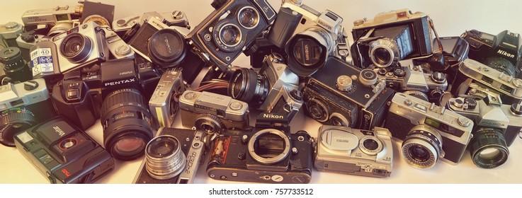 TEL AVIV, ISRAEL, DEC. 02, 2015 : Vintage photo cameras stacked in a heap. Old (35mm film) devices - Niccormat, Fujica,Vitoret, Petri, Kowa, Olympus, Rolleicord, Minolta, Nikon producing in 1940-1975