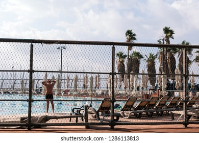 Tel Aviv, Israel -December 1 2018: Man getting ready to get into the water at an urban pool facility.