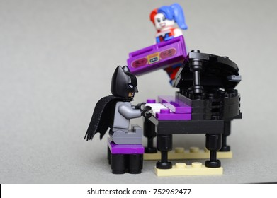 Tel Aviv, Israel - December 24, 2016: Studio shot of LEGO minifigure Batman playing the Piano while Harley Quinn distorb him with a Boombox