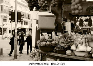 TEL AVIV, ISRAEL - DECEMBER 28, 2017: Urban scene. Fresh detox drink at juice stall. Old ladies cross street and young beautiful woman seen at billboard at other side of street at background. Sepia.