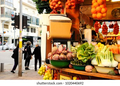 TEL AVIV, ISRAEL - DECEMBER 28, 2017: Urban scene. Fresh detox drink at juice stall. Old ladies cross street and young beautiful woman seen at billboard at other side of street at background.