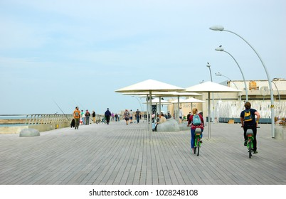 TEL AVIV, ISRAEL - DECEMBER 28, 2017: Young couple riding green bike (Tel-O-Fun bikesharing rental system) exploring Port which is popular recreational and commercial area for locals and tourists.