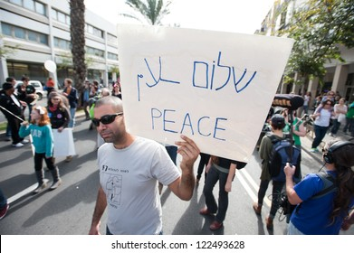 """TEL AVIV, ISRAEL - DECEMBER 7: An activist holds a sign reading """"Peace"""" in Hebrew, Arabic, and English during the annual human rights march in Tel Aviv, Israel, December 7, 2012."""