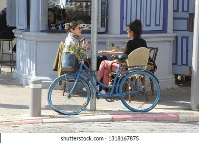 TEL AVIV ISRAEL - February 12, 2019. Young women are sitting on chairs, drinking tea and water at outdoor street cafe terrace with vintage decorated bike on Rothschild Boulevard in Yafo neighborhood.