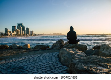 Tel Aviv Israel January 30, 2021 Unidentified people on the beach of Tel Aviv in winter during the lockdown of the city and the Coronavirus outbreak hitting Israel