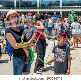 TEL AVIV, ISRAEL - JULY 03, 2015 : Yung families and bubbles during Bubble parade at Habima square in Tel Aviv, Israel.