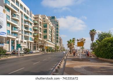TEL AVIV/ ISRAEL - JULY 16, 2008: Highway along embankment with buildings on road side, parking and people walking along on July 16, 2008 in Tel Aviv.