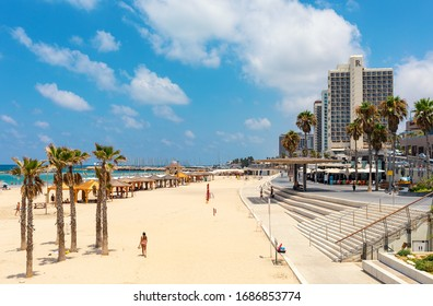 TEL AVIV, ISRAEL - JULY 19, 2017: People on public beach along Mediterranean coastline and promenade with modern hotels in Tel Aviv - second most populous city in Israel.