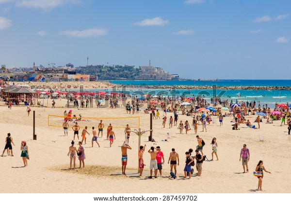 TEL AVIV, ISRAEL - JUNE 12, 2015: View of the beach of Tel-Aviv and the old city of Jaffa, with locals and tourists in Tel-Aviv, Israel.