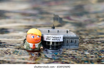 """Tel Aviv, Israel- June 6, 2017: A business man minifigure that resemble Donald Trump standing / drowning next to a White House model decorated with a sign that read """"I Don't Believe in Global Warming"""""""