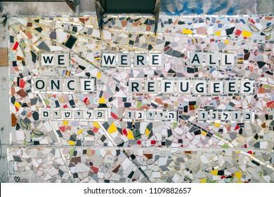"Tel Aviv, Israel - June 7, 2018: Mosaic wall art saying ""We were all once refugees"" in the streets of Tel Aviv, Israel."