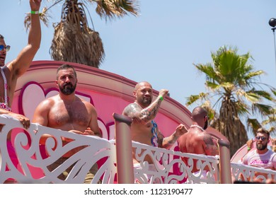Tel Aviv, Israel - June 8, 2018: 20th annual Tel Aviv Pride Week. Muscled gogo boys dancing on the party trucks moving along the beach during the parade.