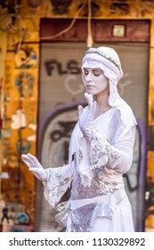 Tel Aviv, Israel - June 8, 2018: Female busking artist performing as a live statue in the entrance of the Carmle Market of Tel Aviv, Israel.