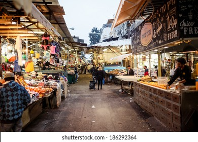 TEL AVIV, ISRAEL - MARCH 23, 2014: Shoppers at the Carmel Market in Tel Aviv on March 24, 2014, Israel. It's one of Israel's oldest outdoor marketplaces offers a wide variety of foods and merchandise.