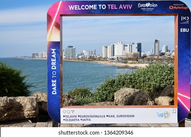 Tel Aviv, Israel - March 5, 2019: Poster on the Jaffa Promenade with official Eurovision symbols Eurovision Song Contest 2019. Tel Aviv skyline and Mediterranean sea on background. Welcome to Tel Aviv