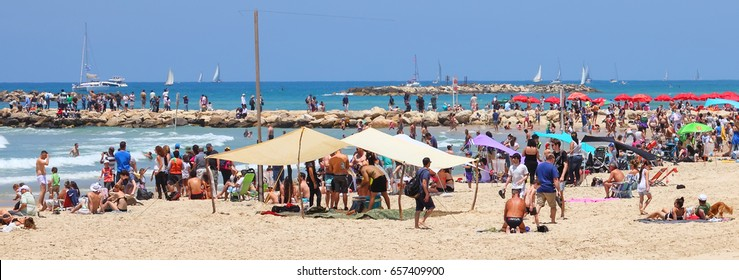 TEL AVIV, ISRAEL - May 02, 2017 : Cheerful people - locals and tourists enjoy a sunny day on sandy beach of Mediterranean sea coast. They sunbathe, swim, relax  and do sport. Panoramic view