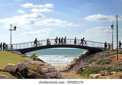 TEL AVIV, ISRAEL - MAY 19, 2014: Pedestrian bridge with pedestrians and cyclists on the promenade in Tel Aviv